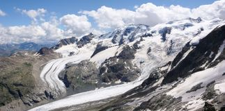 Panorama mountain landscape with high alpine peaks and torn and wild glaciers royalty free stock photo