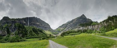 Panorama mountain landscape with lush green forest and several waterfalls. In the Swiss Alps on an overcast summer day stock photos