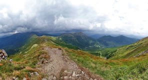 Panorama of mountain ridge from  path running along  top. Mountainside covered with forest Royalty Free Stock Photography