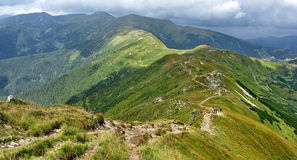Panorama of mountain ridge from  path running along  top. Mountainside covered with forest Stock Image
