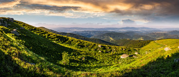 Panorama of mountain ridge with peak at sunset. Panorama of mountain ridge with peak behind the hillside. beautiful summer background at sunset with cloudy sky Royalty Free Stock Photos