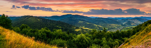 Panorama of mountain ridge with peak at sunset. Panorama of mountain ridge with peak behind the hillside. beautiful summer background at sunset with red sky Royalty Free Stock Image