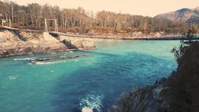 Panorama mountain river, hanging bridge, turquoise water, summer and autumn stock footage