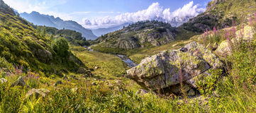 Panorama of mountain scenery with meadow, located in a river val Royalty Free Stock Images