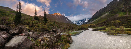 Panorama of a mountain stream, glacier and rocks Stock Image