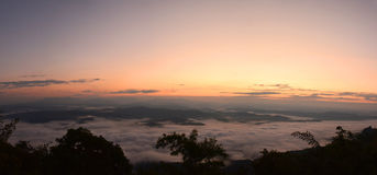 Panorama mountain view at sun rising with mist in the field Stock Image