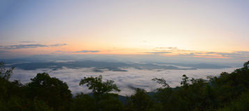 Panorama mountain view at sun rising with mist in the field Royalty Free Stock Photos