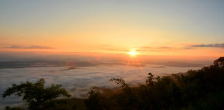 Panorama mountain view at sun rising with mist in the field Royalty Free Stock Images