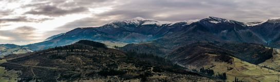 Panorama of mountainous countryside in late autumn. Great Borzhava mountain ridge with snowy Velykyi Verkh peak at sunrise Royalty Free Stock Images
