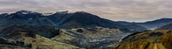 Panorama of mountainous countryside in late autumn. Great Borzhava mountain ridge with snowy tops and villge down the valley at sunrise Royalty Free Stock Photography