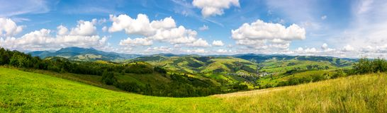 Panorama of mountainous countryside. Lovely countryside scenery in early autumn with grassy field on hillside, village down in the valley and clouds on a blue Royalty Free Stock Image