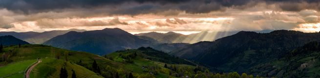 Panorama of mountainous countryside at sunset. Country road through rolling hills in to the distance. heavy clouds over the ridge. beams of lite from the Stock Photos