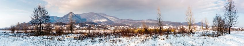 Panorama of mountainous countryside in winter. Trees on snowy meadow not far from the village at the foot of the mountain Royalty Free Stock Photos