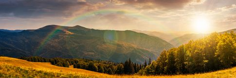 Panorama of a mountainous landscape at sunset. Panorama of a mountainous landscape with rainbow. grassy meadow down the hill in to the forest. lovely summer Stock Images