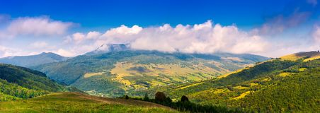 Panorama of mountainous rural area in autumn. Lovely countryside scenery with fluffy clouds above the ridge Stock Photography