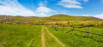 Panorama of mountainous rural area in springtime. Lovely countryside scenery with wooden fence along the country road in the village outskirts stock photos
