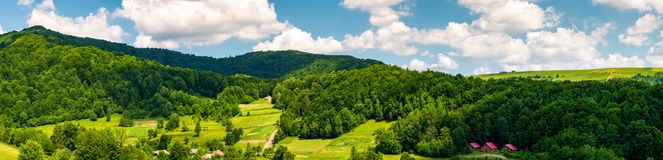 Panorama of mountainous rural area in summer. Beautiful landscape of the forested hill and village in the valley. agricultural fields on grassy slopes under Stock Photo