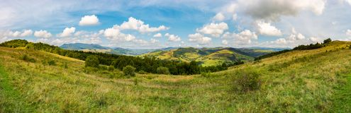 Panorama of mountainous TransCarpathia countryside. Beautiful autumnal landscape. gorgeous cloudscape on a blue sky. forest on the grassy hill. Pikui mountain Royalty Free Stock Image