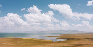 Panorama with mountains and blue lake Son Kul in Kyrgyzstan under white clouds. Panorama with lake and blue cloudy sky above Royalty Free Stock Images