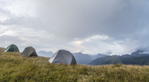 Panorama of the mountains, in a clearing, there are three tents Royalty Free Stock Image