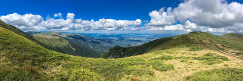 Panorama of mountains and clouds. Panorama of a grassy ridge and plateau above steep mountains valleys under a picturesque blue sky with fluffy white cumulus Royalty Free Stock Photography