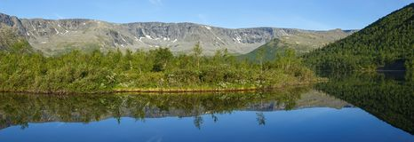 Panorama with the mountains of the Khibiny,. Sky reflected in the lake Small Vudyavr. Kola Peninsula, Russia Stock Image