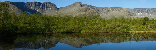 Panorama with the mountains of the Khibiny. Sky reflected in the lake Small Vudyavr. Kola Peninsula, Russia Stock Images