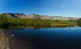 Panorama with the mountains of the Khibiny, sky reflected. In the lake Small Vudyavr. Kola Peninsula, Russia Stock Photos