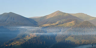 Panorama of mountains at misty sunrise Royalty Free Stock Image