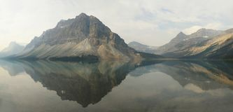 Panorama of the Mountains Reflected in Bow Lake Alberta, Canada. Panorama of the Mountains Reflected In Bow Lake Patially Obscured by Smoke and Clouds Alberta Royalty Free Stock Images
