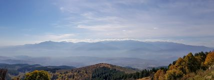 A panorama of mountains silhouette with mist. stock photos