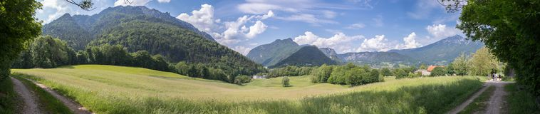 Panoramic idyll: Grass and meadow, mountains and blue sky. Bad Reichenhall, Bavaria, Germany. Panorama of mountains, sky and meadow in Bavaria near Bad royalty free stock image