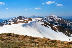 Panorama with mountains. The top of the hills covered with snow. The lawn with dried grass. Tourist resting place. Spring day. Panorama with mountains. The top royalty free stock image