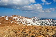 Panorama with mountains. The top of the hills covered with snow. The lawn with dried grass. Tourist resting place. Spring scenery. Panorama with mountains. The stock image