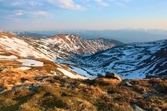 Panorama with mountains. The top of the hills covered with snow. The lawn with dried grass. Tourist resting place. Spring scenery. Panorama with mountains. The stock images