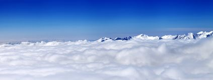 Panorama of mountains under clouds at nice sun day Stock Images