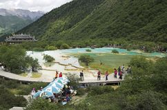 Panorama of multi-colored ponds with tourists on boardwalk and temple in background stock photography