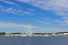 Panorama of National Harbor with Ferris and yachts at pier in Maryland, USA. National Harbor waterfront under blue skies with scenic clouds and Ferris on a pier Royalty Free Stock Photography