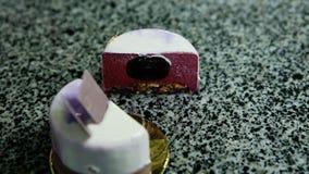 Panorama neer bij besnoeiing in half purpere verglaasde mousse minicake stock videobeelden