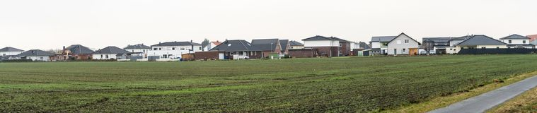 Panorama of a new housing estate with single-family houses on the edge of a village with arable land, lots of space and width as a. Header for a website Stock Images