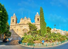 Panorama with church and garden, Birgu, Malta. Panorama with nice landscaped garden of Freedom monument with cactus plants and tall cypress, behind it located Royalty Free Stock Image