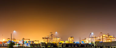 Panorama of night at industrial port. Cranes with cargoes containers and truck at industrial port in night Royalty Free Stock Image