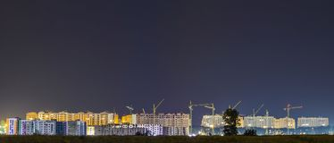 Panorama night view of many building cranes at construction site Stock Photography
