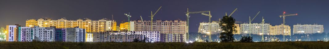 Panorama night view of many building cranes at construction site Stock Image