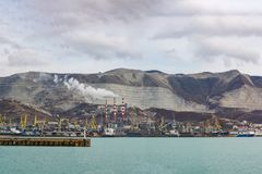Panorama of Novorossiysk cargo port and Smoking chimneys of a cement plant of JSC Novoroscement  in the background of Markotkh rid. Russia, Novorossiysk Royalty Free Stock Photography