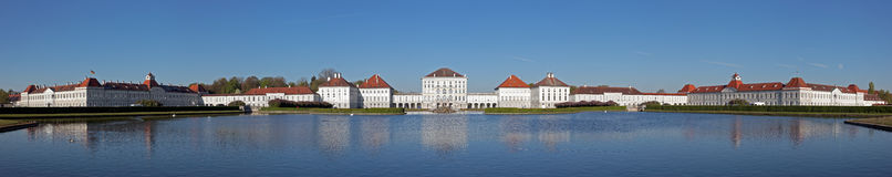 Panorama of  Nymphenburger Castle in Munich. Complete Panorama of  Nymphenburger Castle in Munich with clear blue sky and lake in the foreground Royalty Free Stock Photography