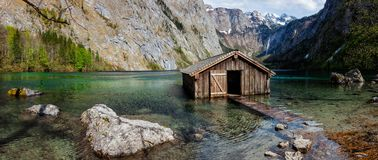 Panorama of Obersee mountain lake in Alps. Panorama of Obersee mountain lake with boat dock hangar in Alps. Bavaria, Germany Royalty Free Stock Photo