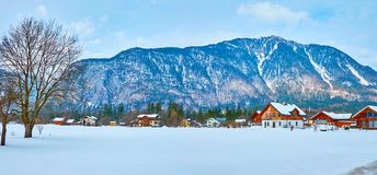 Panorama of Obertraun village, Salzkammergut, Austria. Panorama of Obertraun with numerous wooden cottages and large snowbound field on the foreground royalty free stock photo
