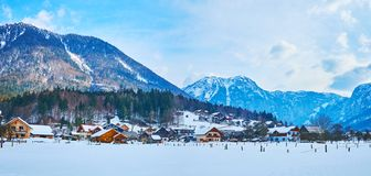 Panorama of Obertraun village, Salzkammergut, Austria. Panorama of the snowbound valley with small wooden houses of Obertraun tourist village, located at the stock photos