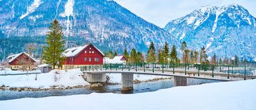 Panorama of Obertraun winter landscape, Salzkammergut, Austria. Panorama of Obertraun village from the snowy bank of Traun river with green pines and huge Alps stock images